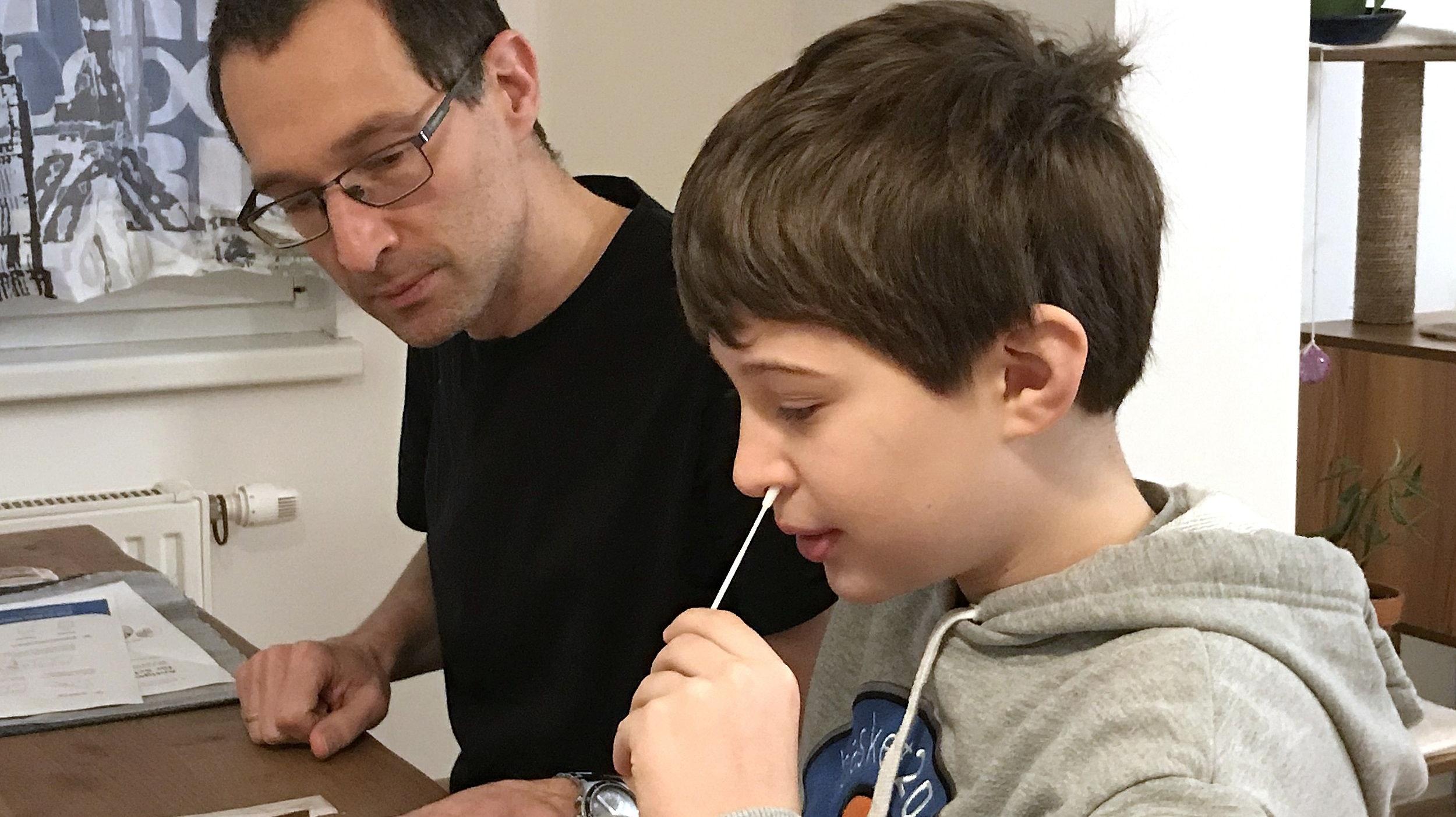 Test zuhause: Ein Schüler nimmt einen Abstrich aus seiner Nase unter Aufsicht seines Vaters. Foto: dpa/Oberkofler