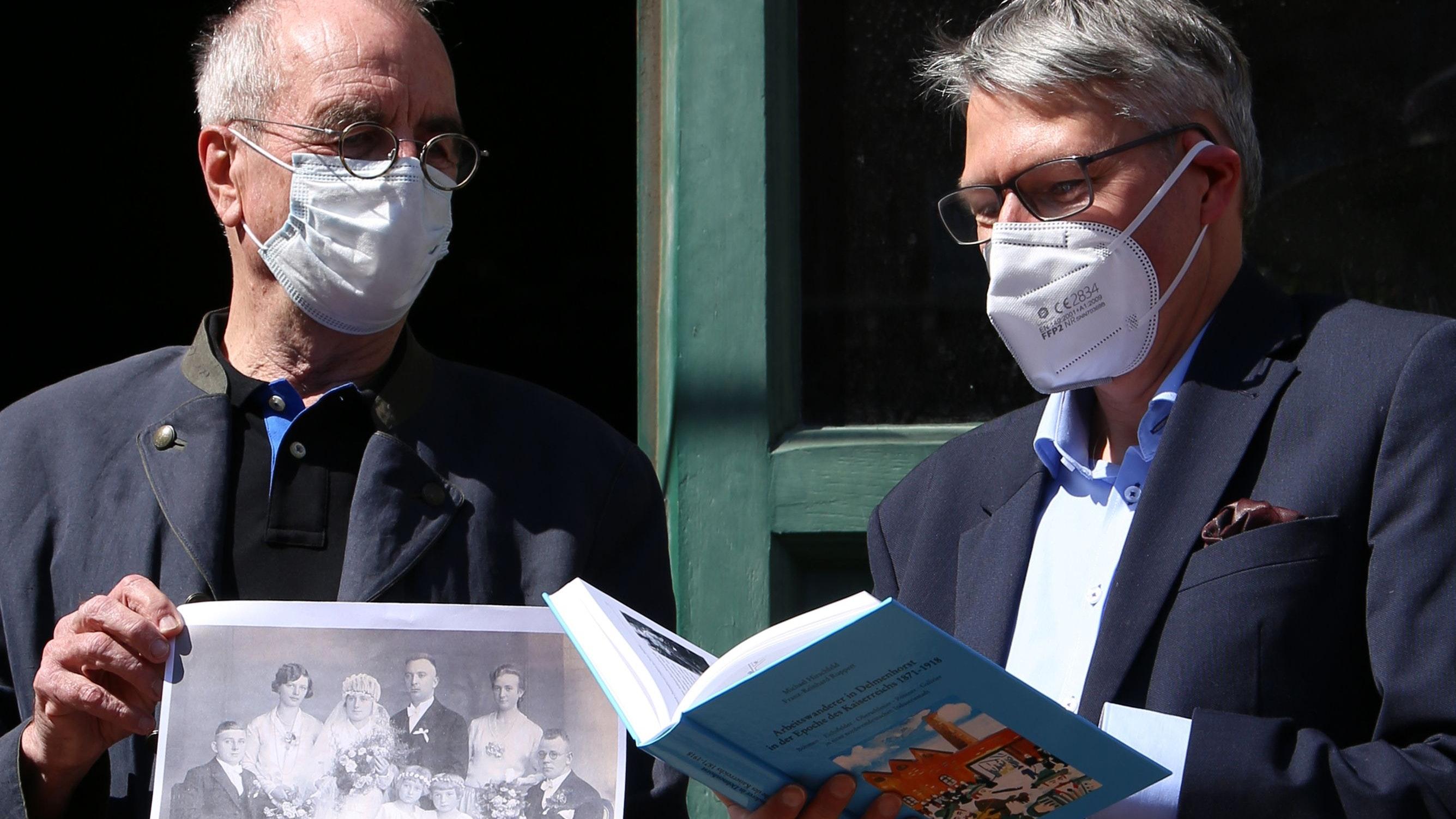 Präsentation vor dem Nordwolle-Museum: Professor Dr. Michael Hirschfeld und Dr. Franz-Reinhard Ruppert (links) stellen ihr neues Buch vor und verweisen anhand eines Fotos sogar darauf, dass sie – entfernt – verwandtschaftlich verbunden sind. Foto: Kathe