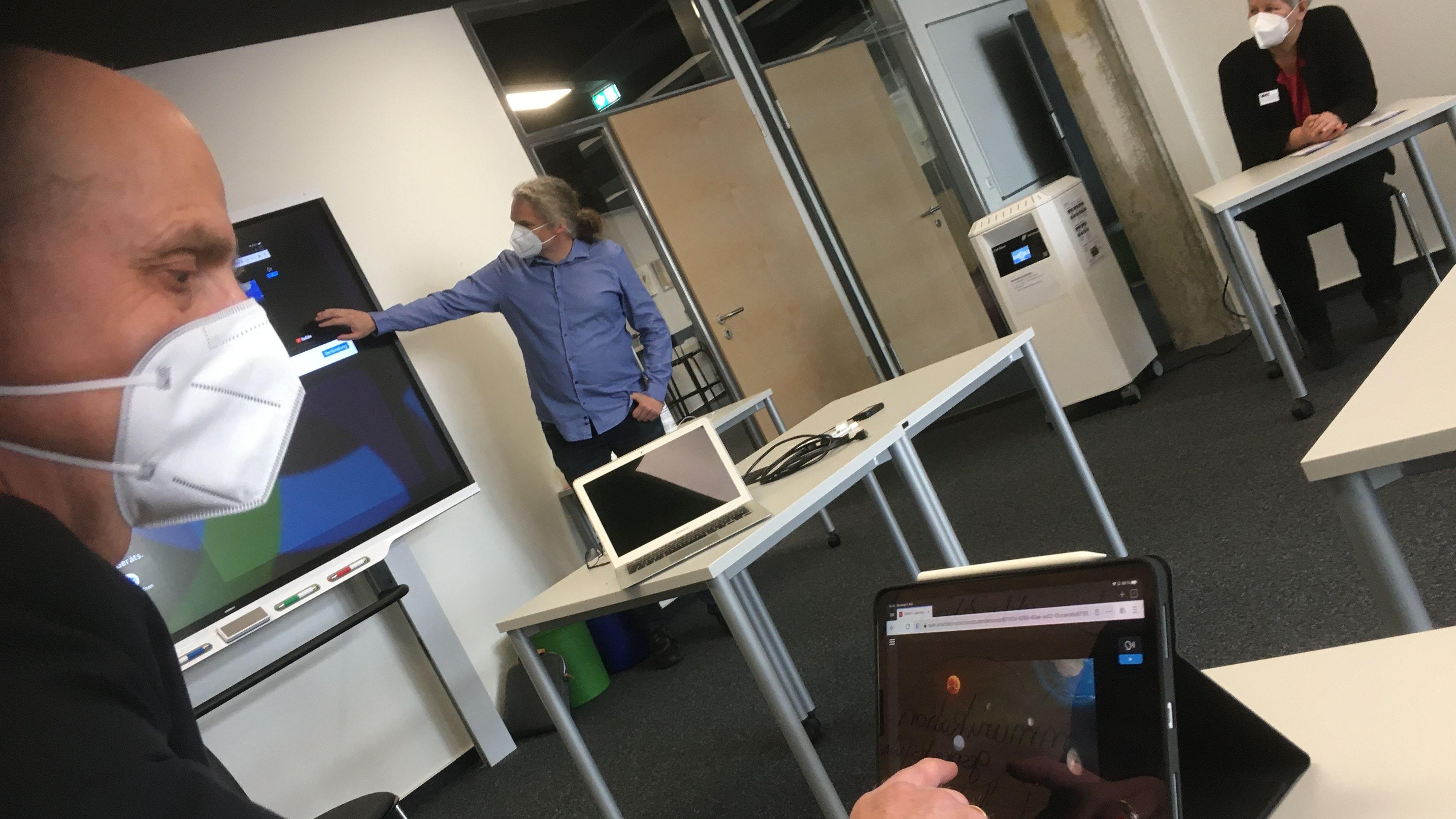 Probelauf in der VHS: Uwe Schöpperle tippt die Aufgabe an, das Smartboard zeigt sie. Im Hintergrund Maik Riecken und Kathrin Würdemann. Foto: Kreke