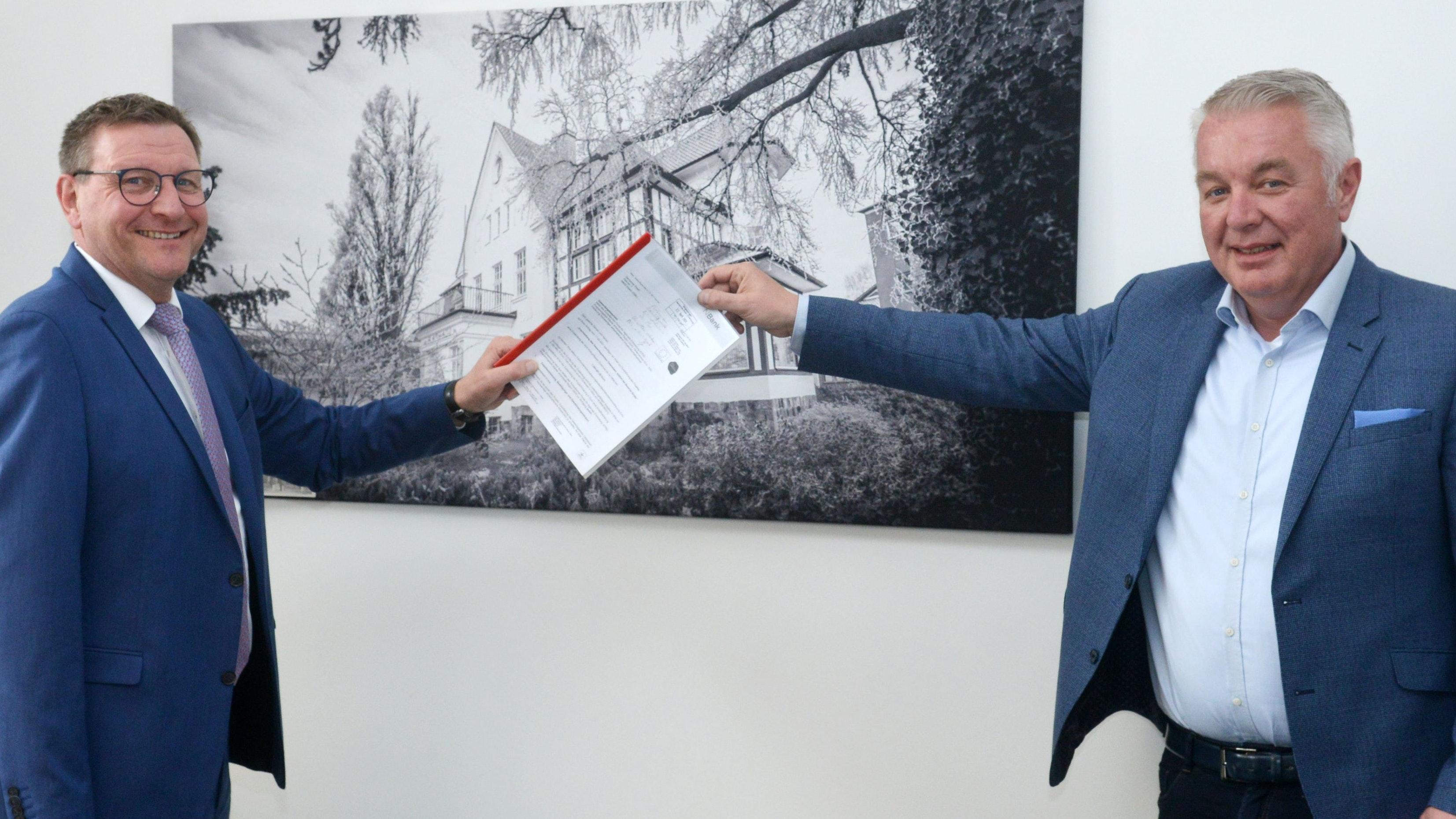 """Christoph Eilers (rechts) überreicht Bürgermeister Kressmann den Förderbescheid über 1,6 Millionen Euro für das Gewerbegebiet """"Osteressen"""". Foto: Siemer"""