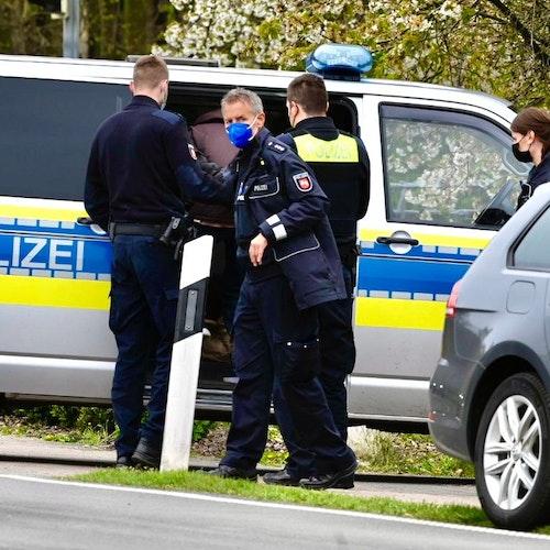 Festnahme in Schledehausen: Ein Mann wird in Handschellenzum Polizei-Bulli geführt. Foto: M. Niehues