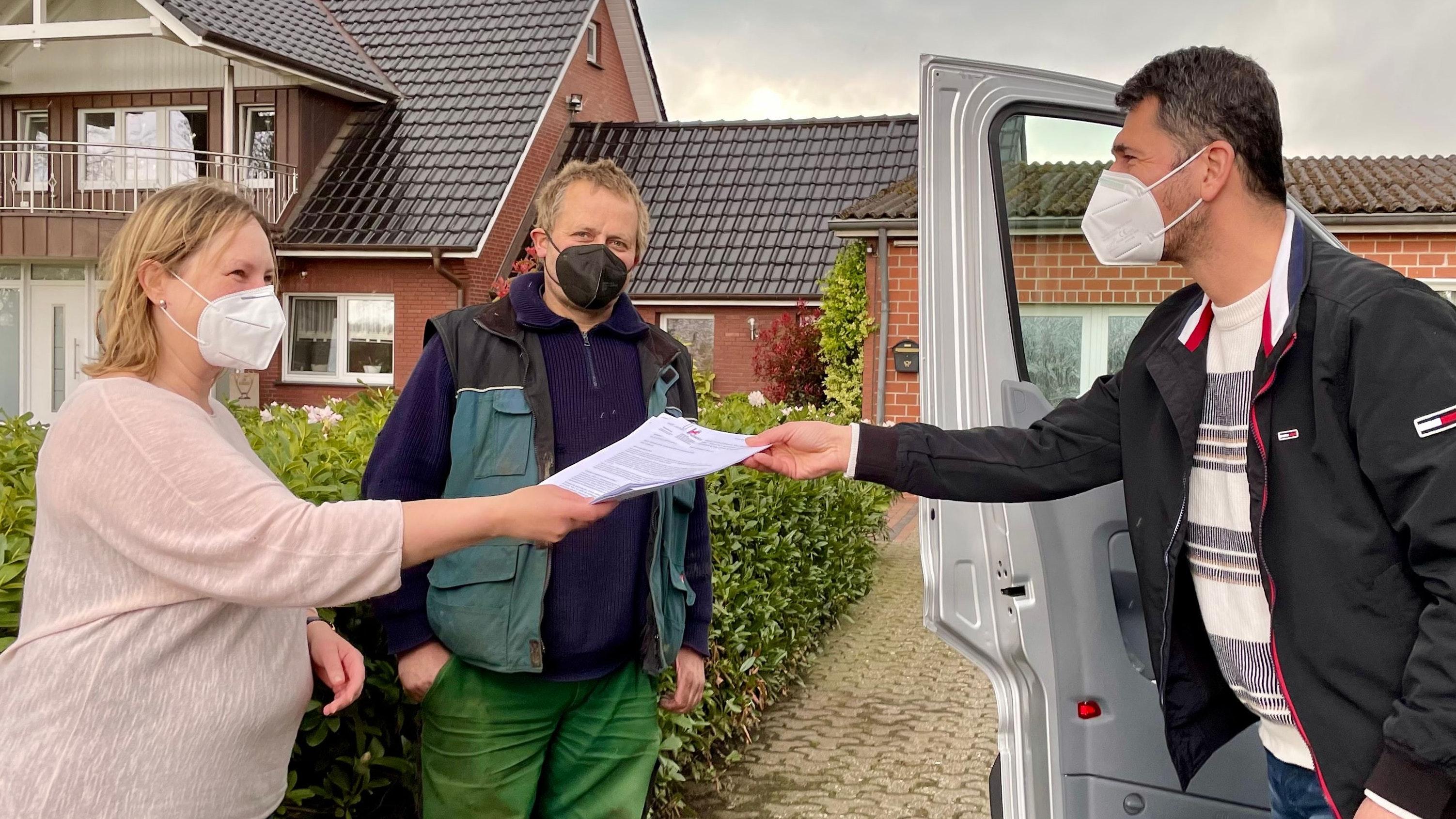 Begrüßen die Initiative der Stadt Vechta und des Landkreises: Das Ehepaar Geerken in Deindrup nimmt die Infoblätter zur Impfkampagne von Ferdi Karatas (rechts) entgegen. Foto: M. Niehues