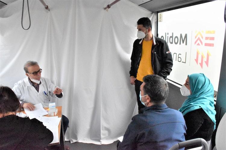 Vor der Impfung steht das Aufklärungsgespräch im Bus: (von links) Dr. Akram El-Harake, Vechtas Integrationsbeauftragter Ferdi Karatas und die Eheleute Akhamur. Foto: Kühn