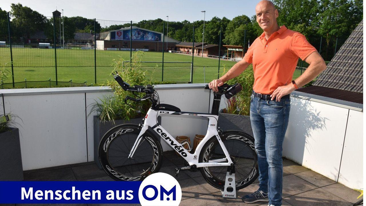 Wohnort direkt am Stadion: Markus Vocks mit seinem Rennrad und dem Sportplatz sowie der Sporthalle des SV Handorf-Langenberg im Hintergrund. Foto: Klöker