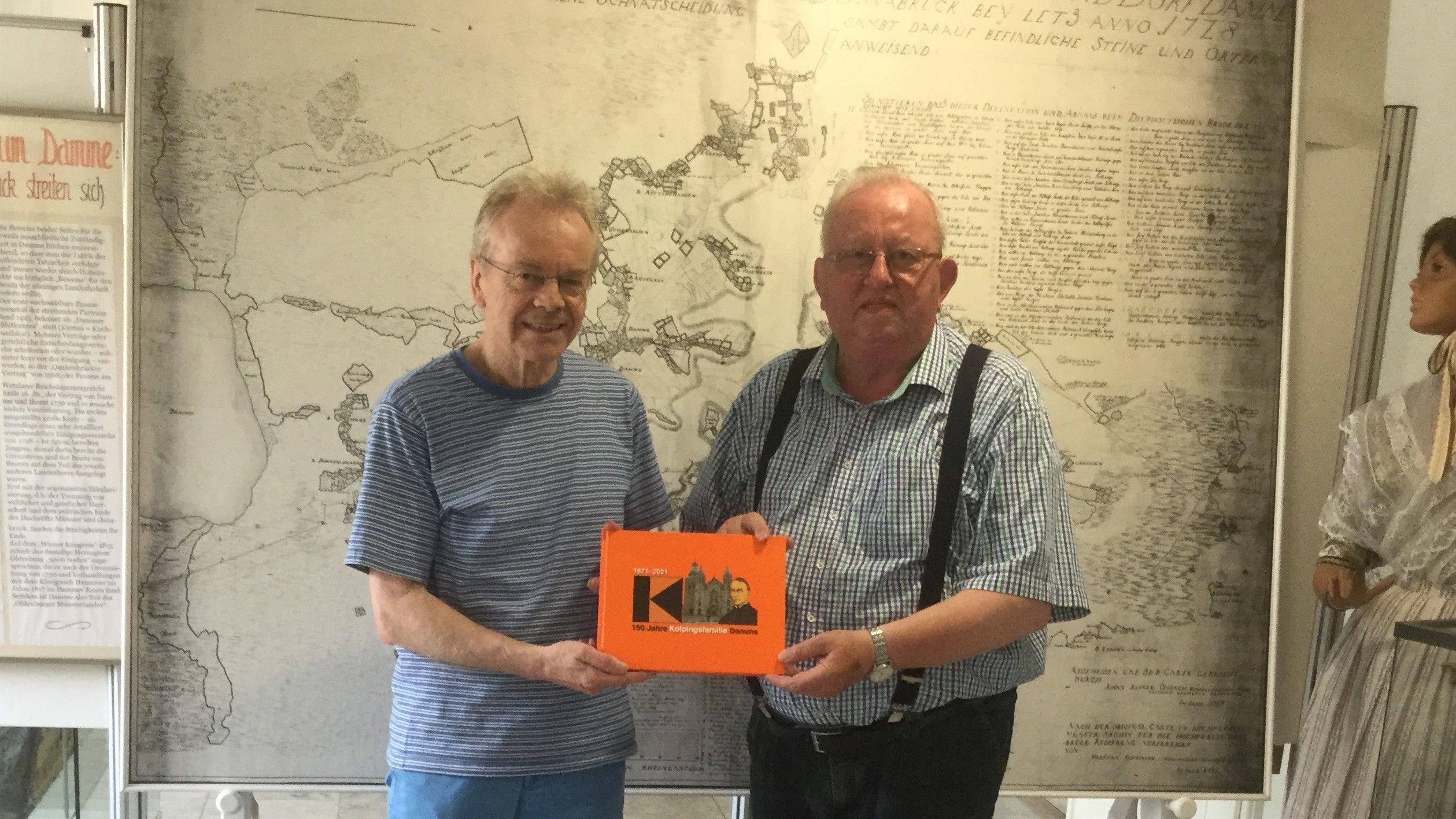 Freude: Kolpingvorsitzender Norbert Grafemeyer (r.) überreicht ein Exemplar der Festschrift an Museumsleiter Wolfgang Friemerding vor historischer Kulisse. Foto: Stadtmuseum