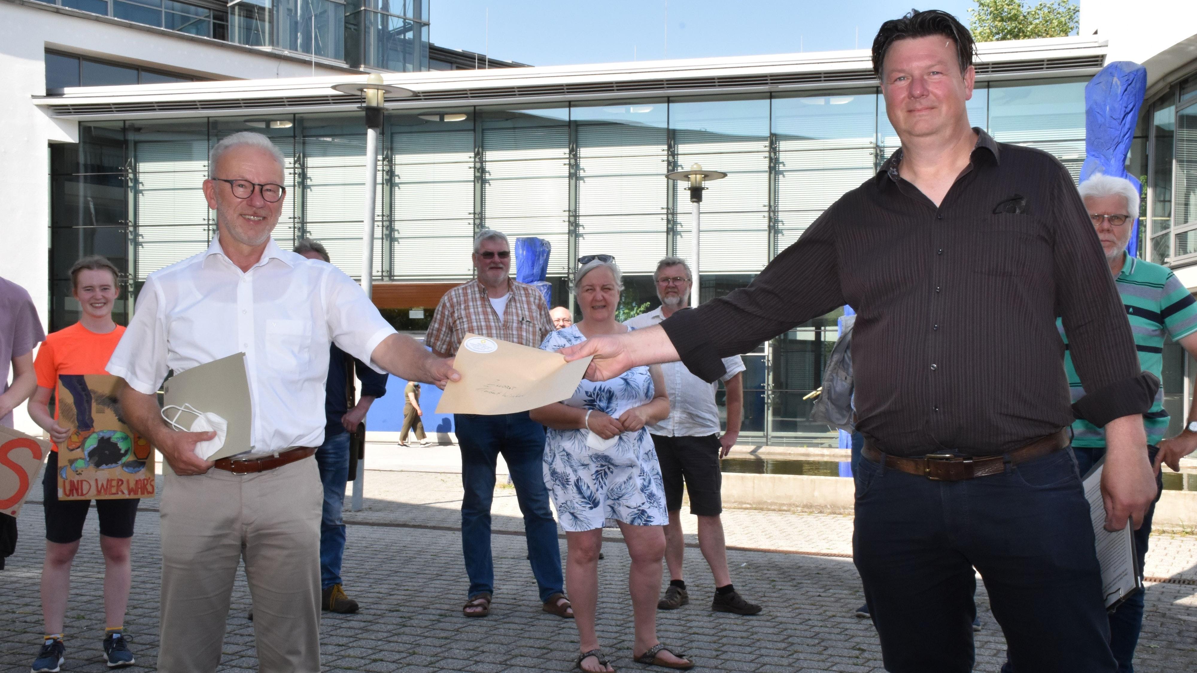 Drei Seiten mit Forderungen: Lokale Klimaschützer um Holger Ziefus (rechts) sowie Ulrich Heitmann, Annette und Heinz Hanken (Hintergrund) übergaben Landrat Hebert Winkel einen offenen Brief. Foto: Berg
