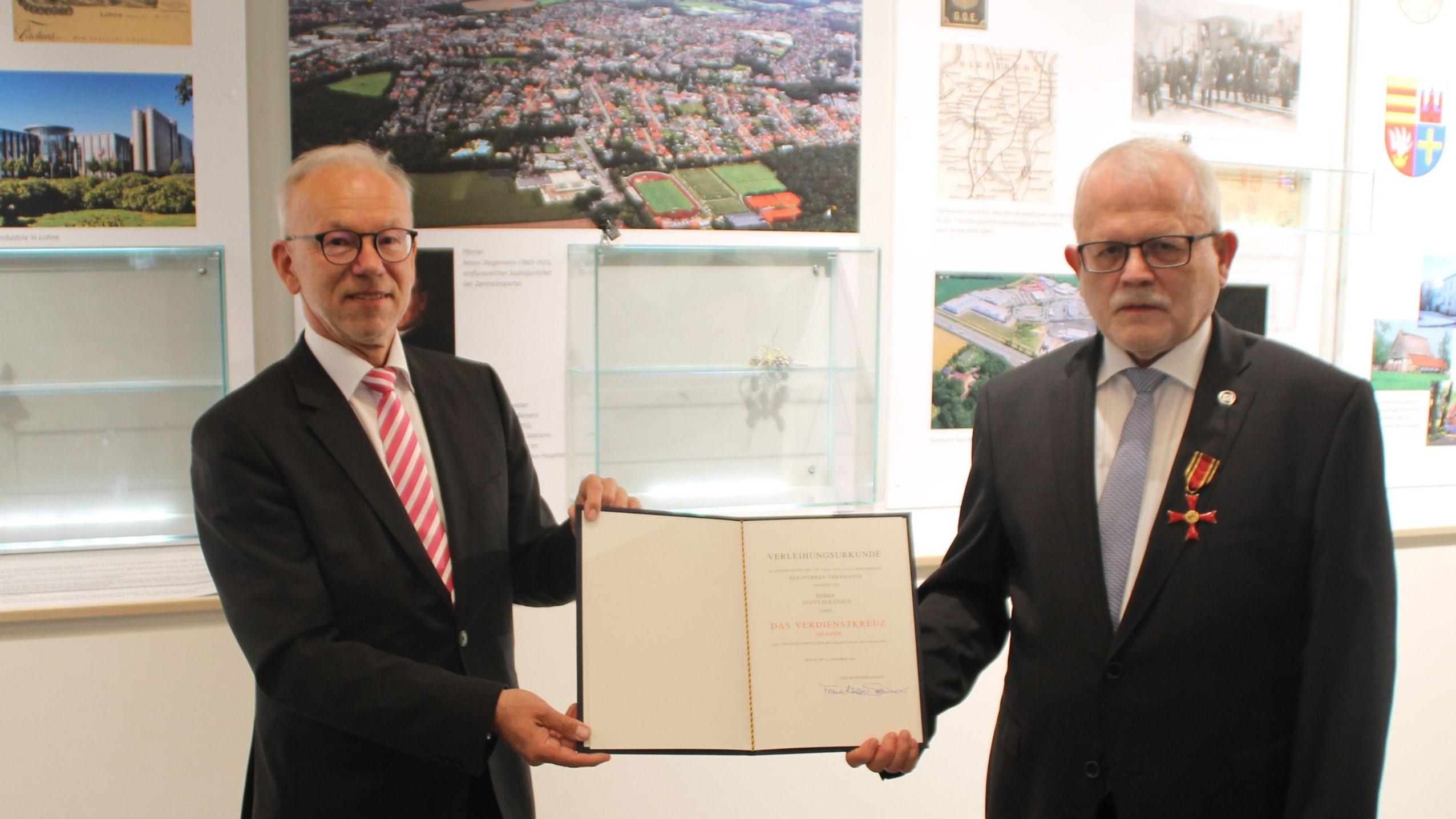 Feierliche Verleihung des Bundesverdienstkreuzes: Landrat Herbert Winkel (links) überreichte Aloys Holthaus die Urkunde sowie den Orden. Foto: Kessen