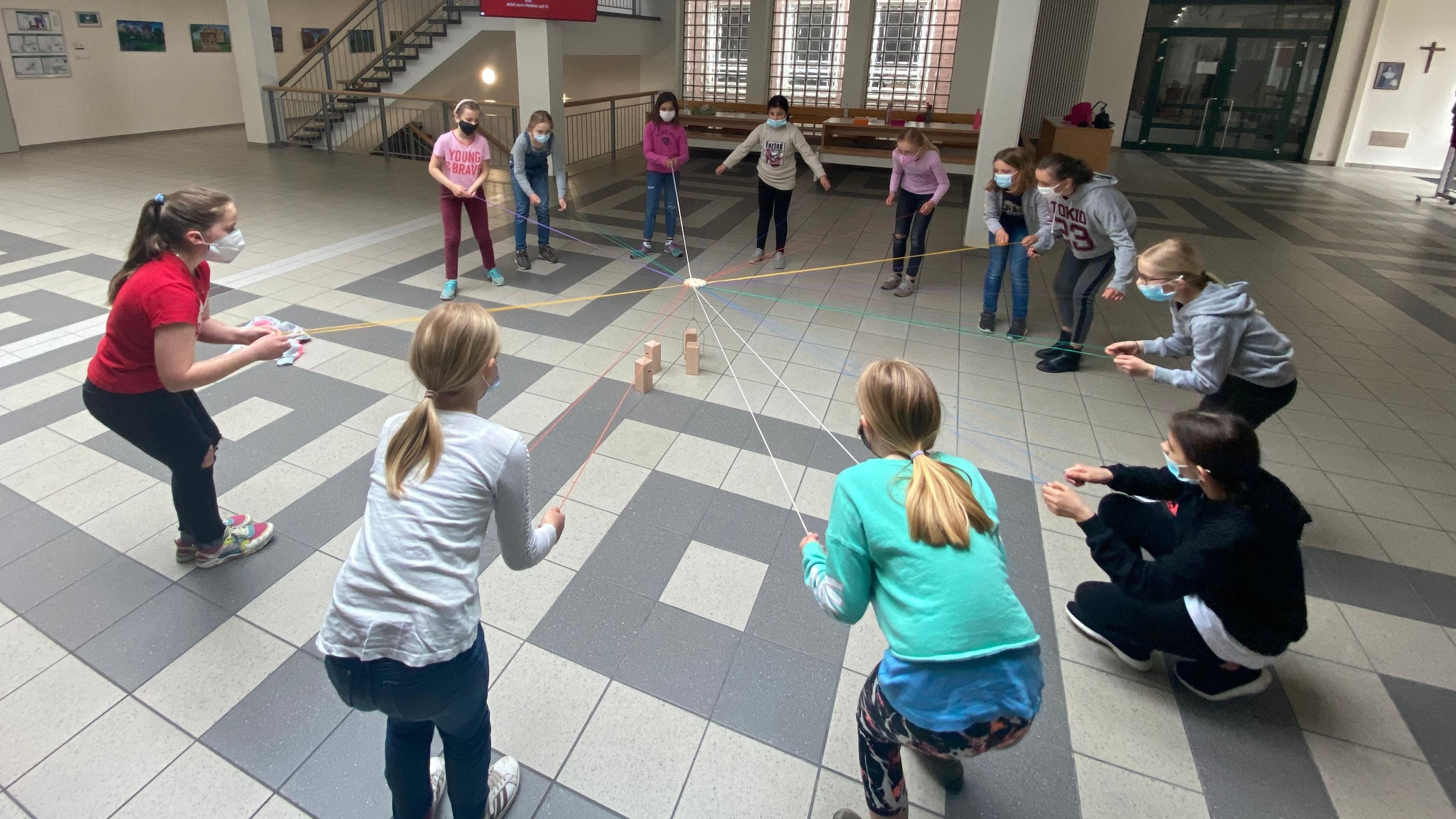 """Die Bedeutung von Zusammenarbeit erfahren die 11 Grundschülerinnen bei dem Spiel """"Turmbau"""", denn nur gemeinsam können sie das Ziel erreichen. Foto: C. Fischer"""