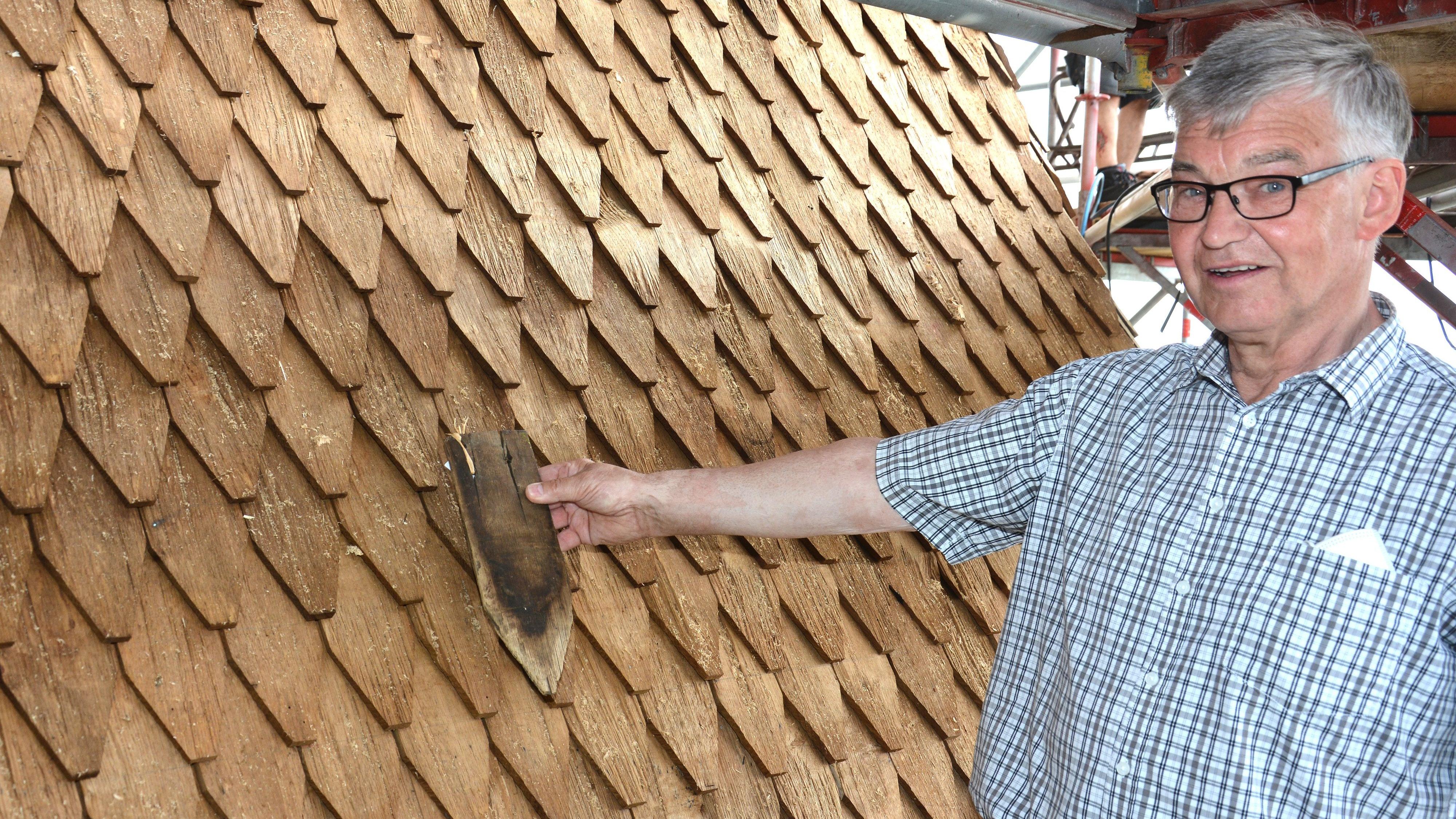 Aus alt wird neu: Vereinsvorsitzender Karl-Heinz Schnieder mit einer der Schindeln der alten Mühle vor dem Hintergrund mit dem neuen Material. Foto: Sperveslage