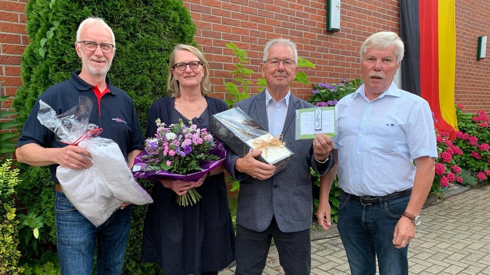 Abschied mit Lob: Liedervater  Winfried Schulz (rechts) und Stellvertreter Carsten Afflerbach (links) danken Klaus Wolf (mit Partnerin Christine). Foto: Siemer