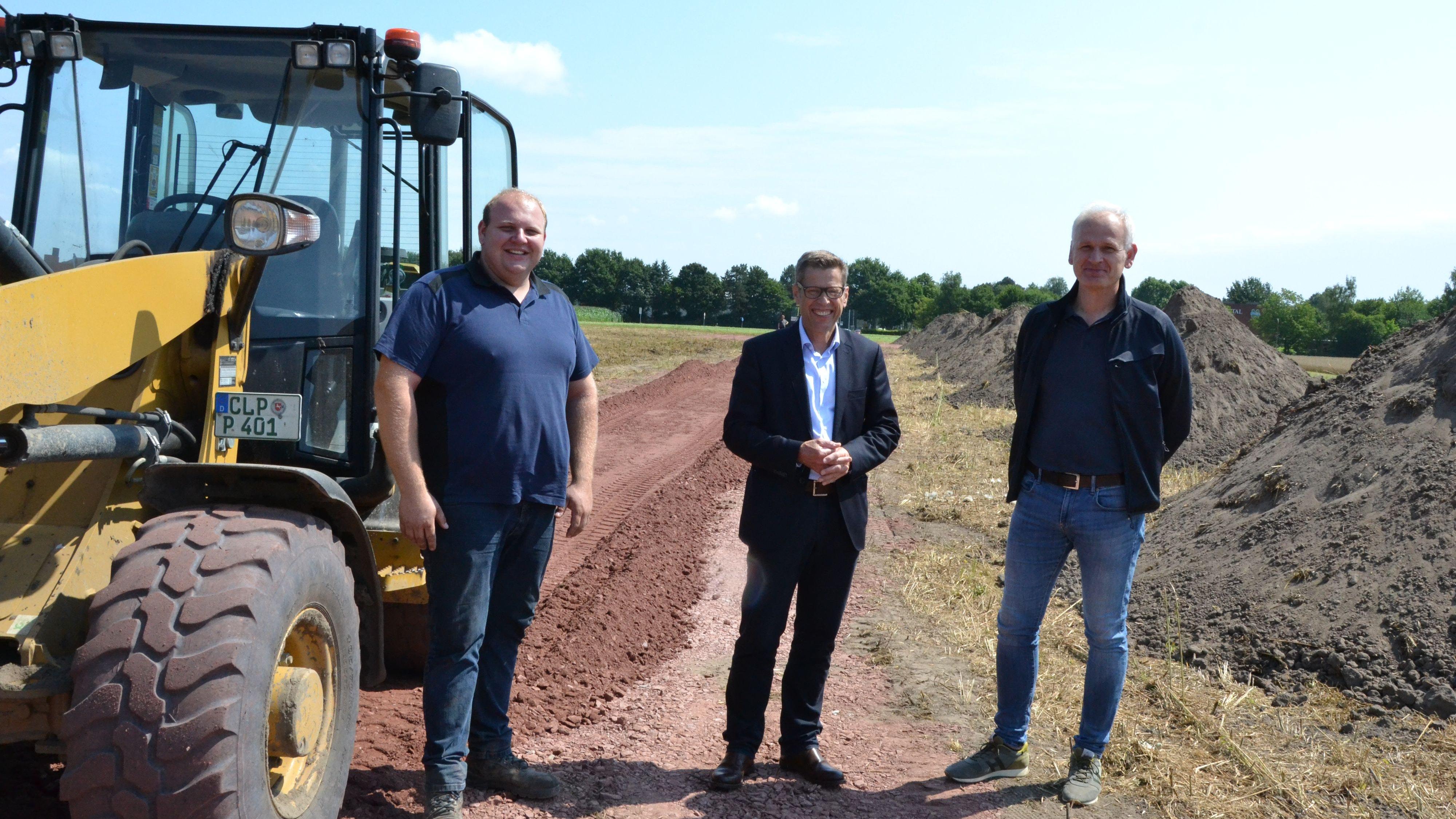 Erster Schritt: Patrick Poppe (von links) hat die Verbindungsstraße angelegt. Bürgermeister Marcus Willen und Jens Flerlage (Tiefbauamt) kümmern sich um die weiteren Planungen. Foto: G. Meyer
