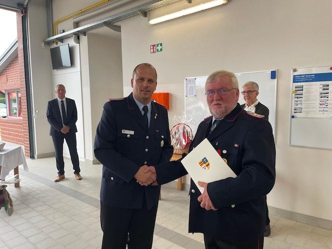 Ehrung: Kreisbrandmeister Stefan Abshof bedankt sich bei Albert Wilken (rechts). Foto: Steven FeilerFFW Lastrup