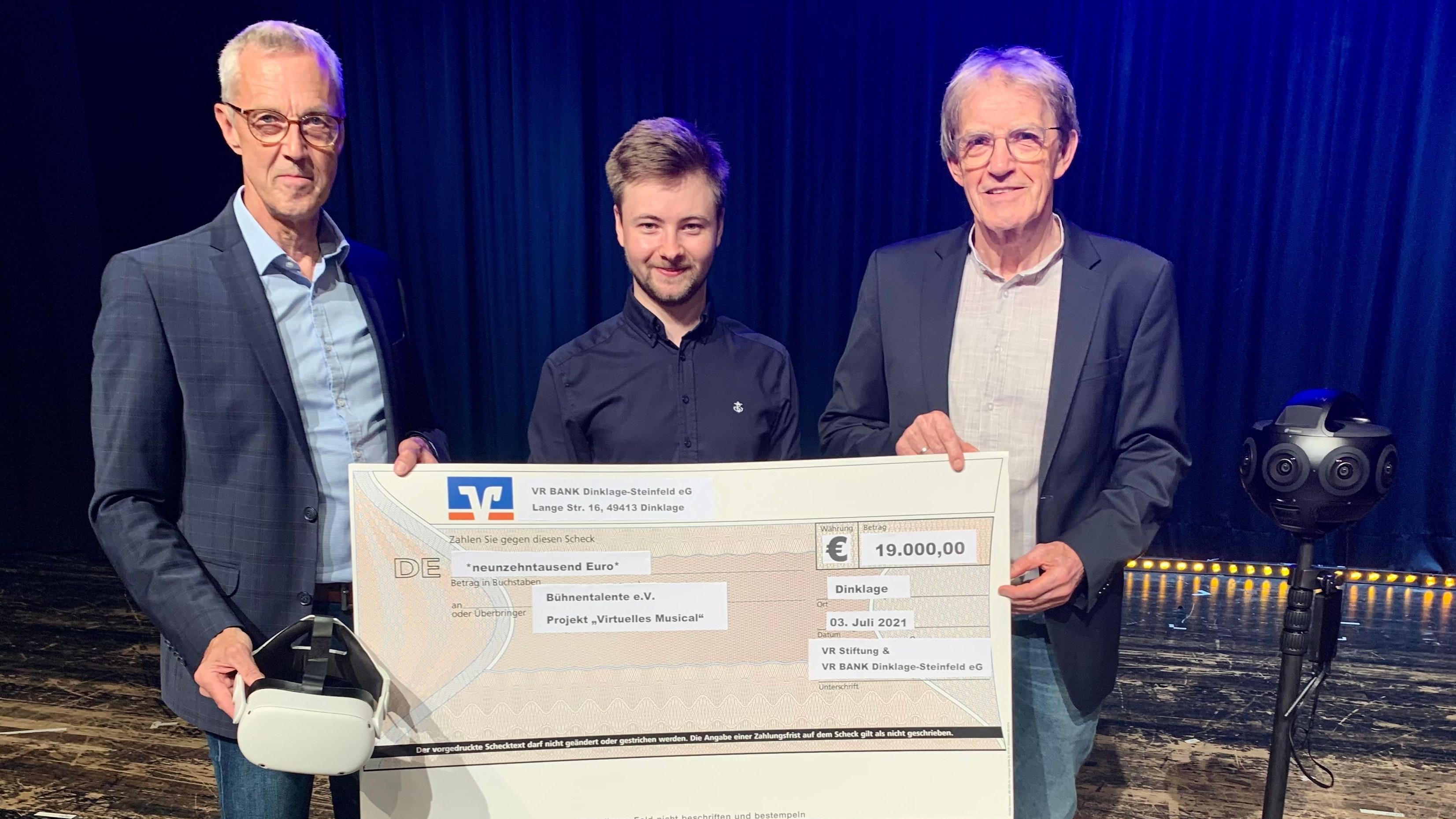 Großzügige Unterstützung: VR-Bank-Vorstand Benno Fangmann (links) übergab Vincent Kaufmann (Mitte) und Werner Fangmann von den Bühnentalenten am Samstag während der Generalprobe einen symbolischen Scheck in Höhe von 19.000 Euro. Foto: Stilkenböhmer