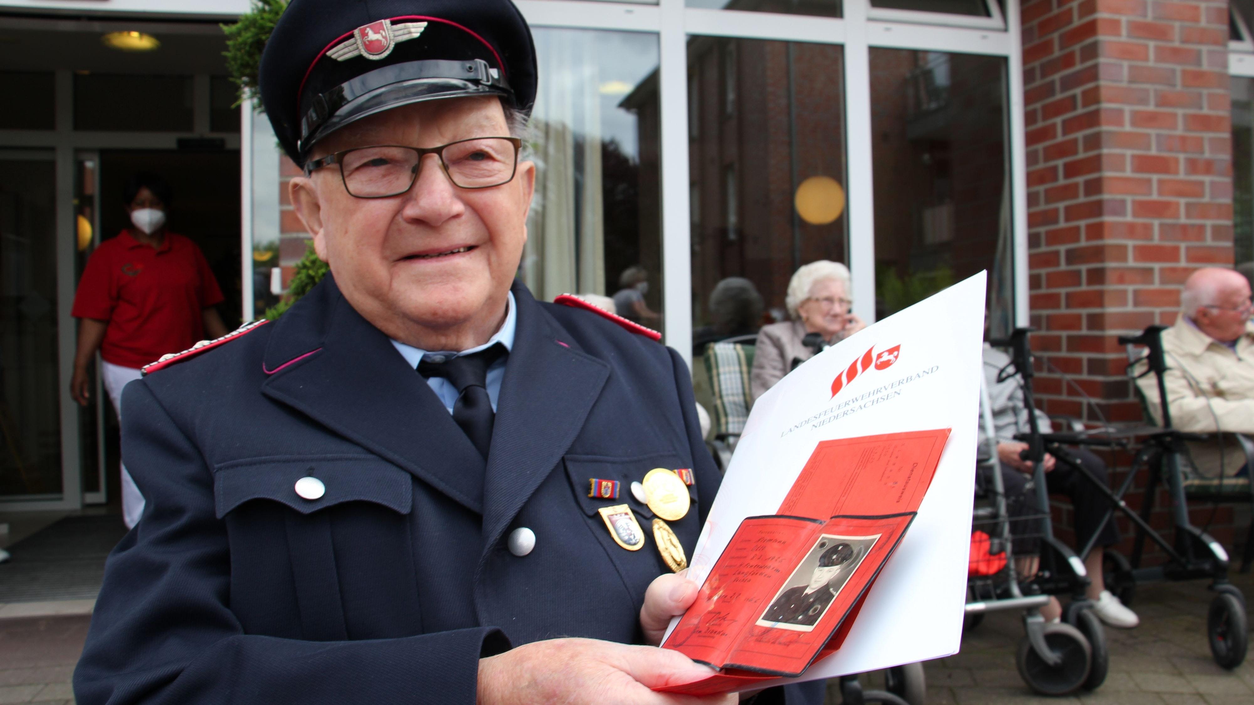 Otto Niemann kann auf die Auszeichnung für seine langjährige Mitgliedschaft stolz sein. Neben der Urkunde hält der Jubilar seinen uralten Feuerwehrausweis in den Händen. Foto: Speckmann
