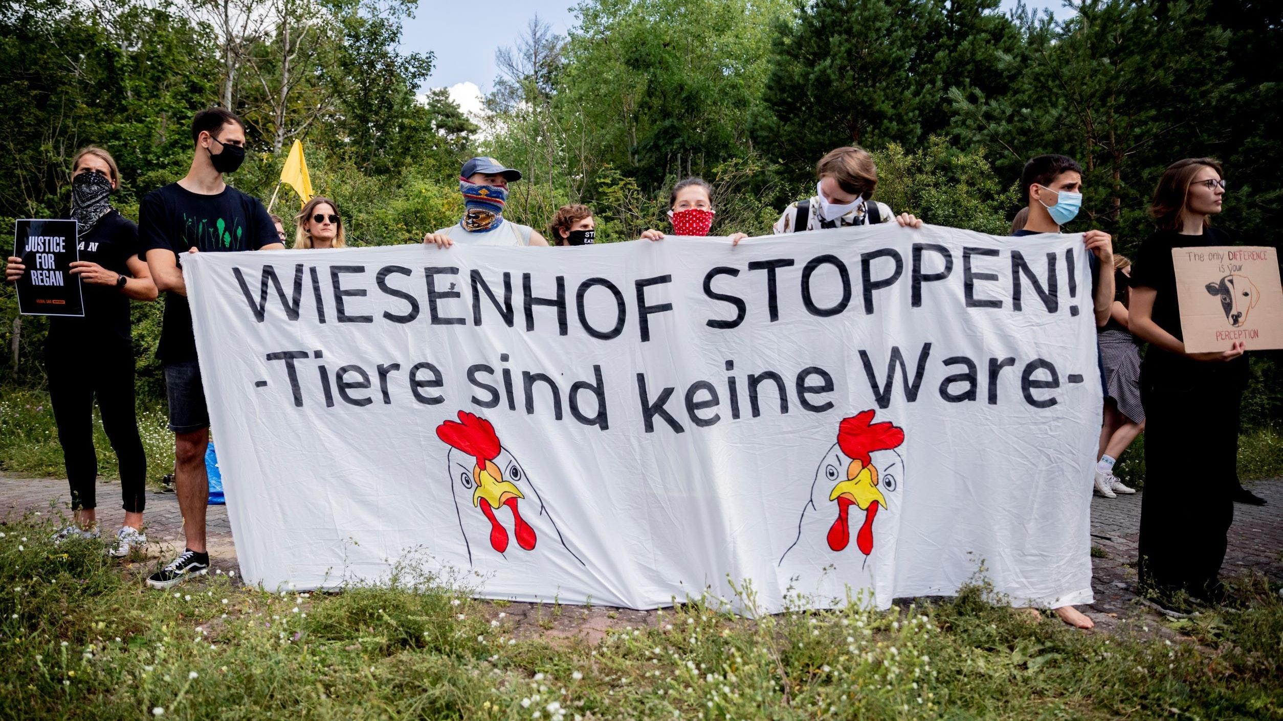 """Tierschutzaktivisten halten 2020 bei einer Blockade des Wiesenhof-Schlachthofs in Niederlehme nahe Königs Wusterhausen ein Banner mit der Aufschrift """"Wiesenhof stoppen! - Tiere sind keine Ware"""" hoch. Symbolfoto: dpa"""